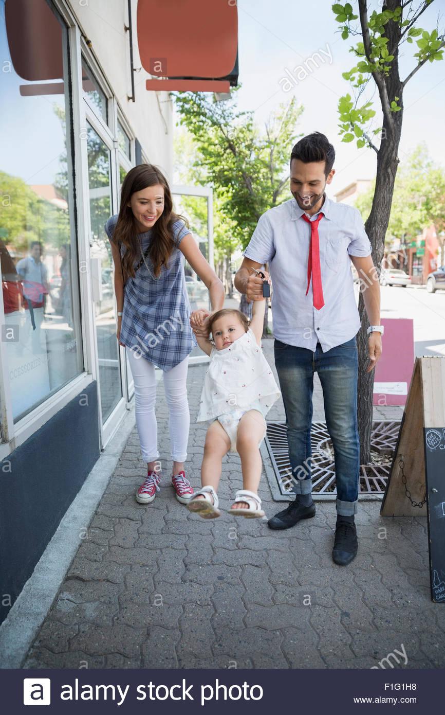 Los padres hija oscilante sobre acera Imagen De Stock