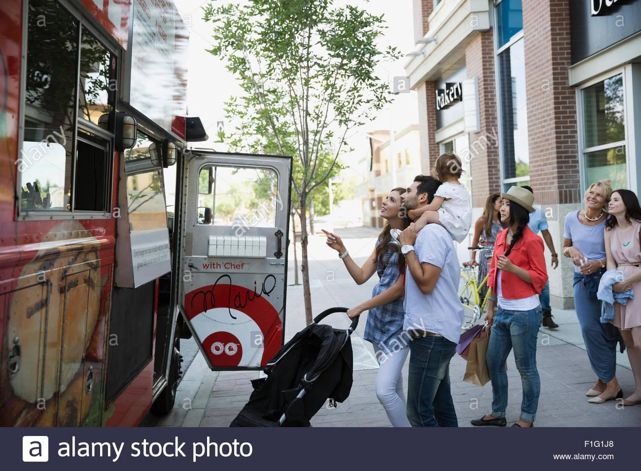 Clientes fuera de camión de alimentos sobre la acera Imagen De Stock