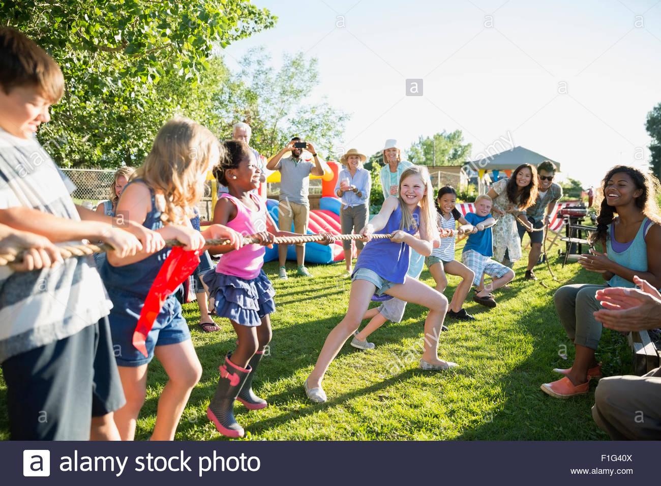 Vecinos animando niños jugando tug-of-war park Imagen De Stock