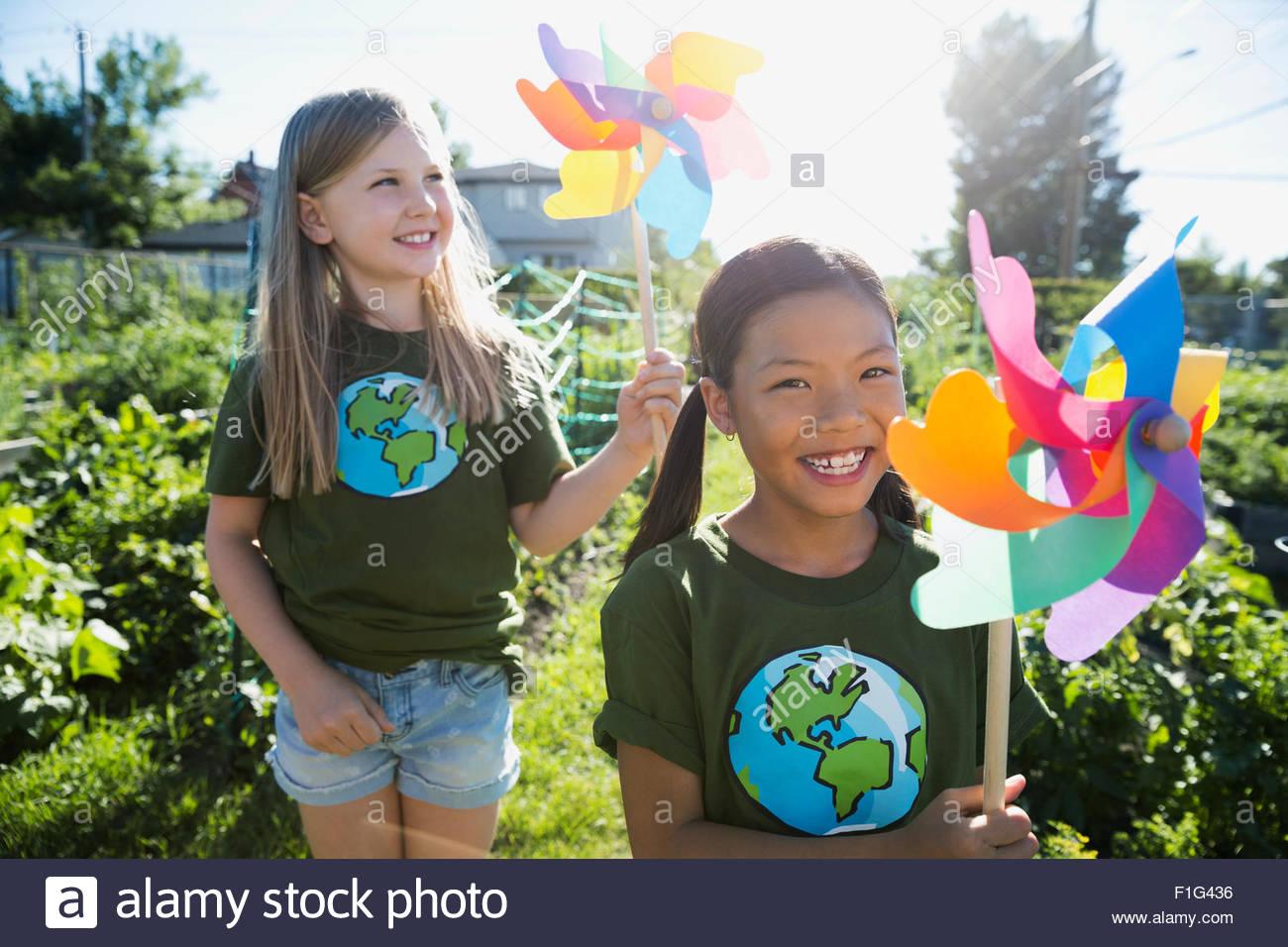 Retrato de niñas sonrientes con molinetes en el soleado jardín Imagen De Stock