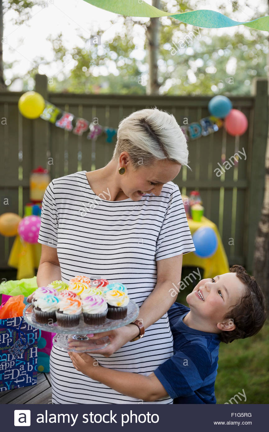 Hijo abrazarse madre sosteniendo pastelitos en cake stand Imagen De Stock