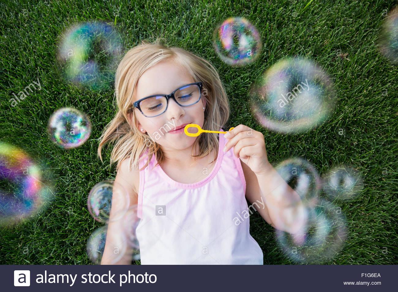 Vista aérea chica rubia con anteojos soplando burbujas Imagen De Stock