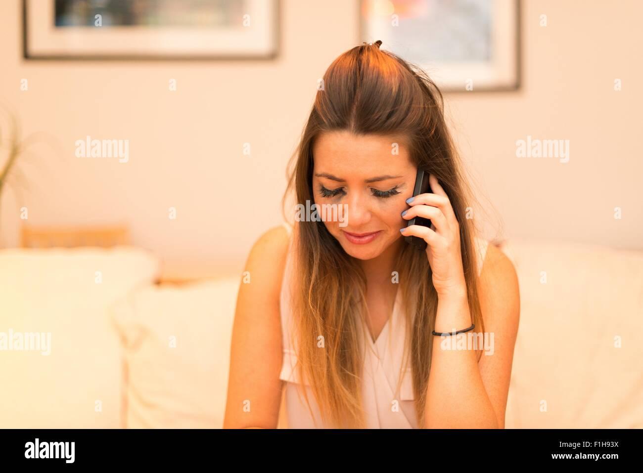Mujer joven tener conversación telefónica, llorando Imagen De Stock