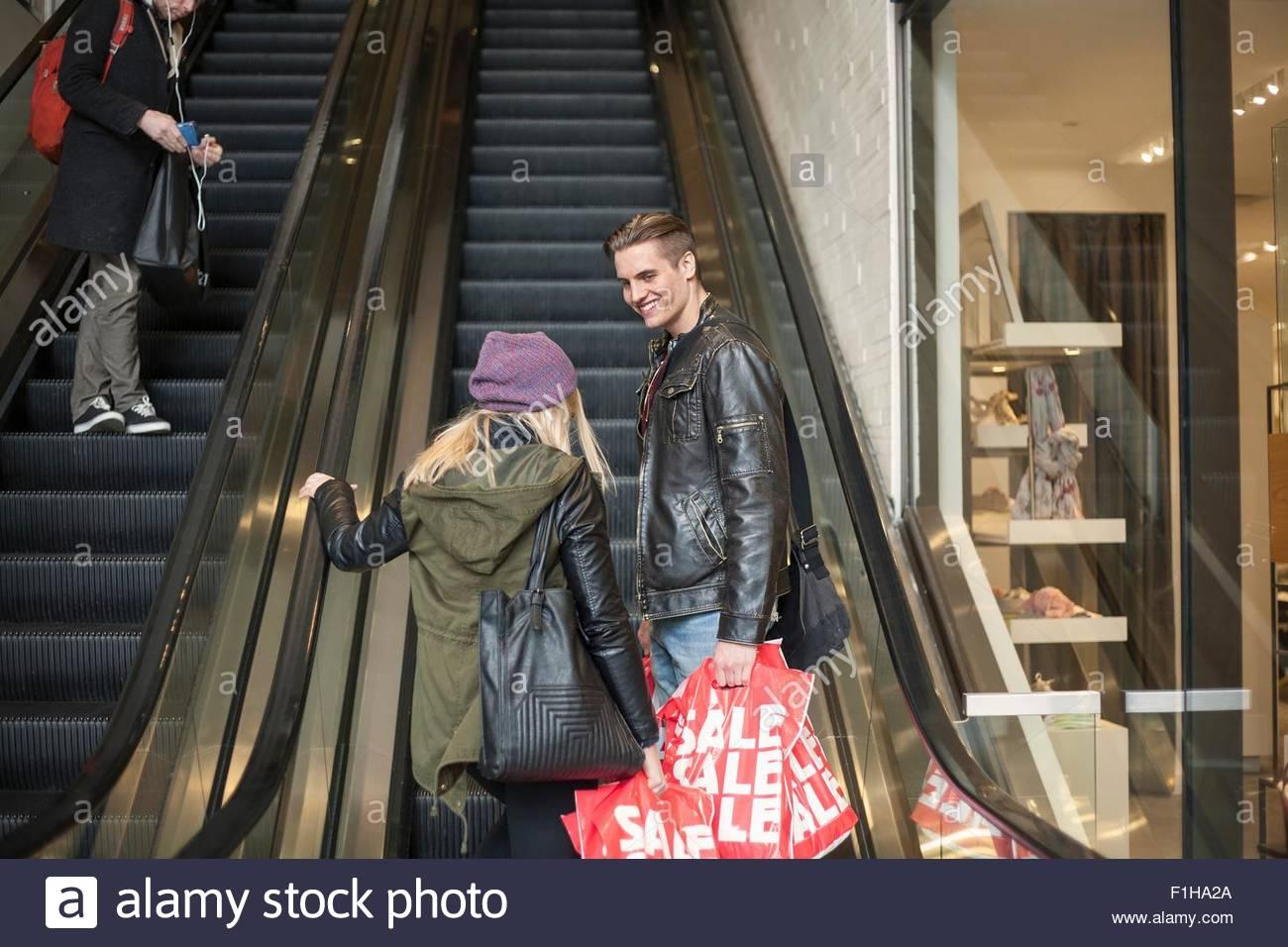 Pareja joven subiendo escaleras con bolsas de compras, Nueva York, EE.UU. Imagen De Stock
