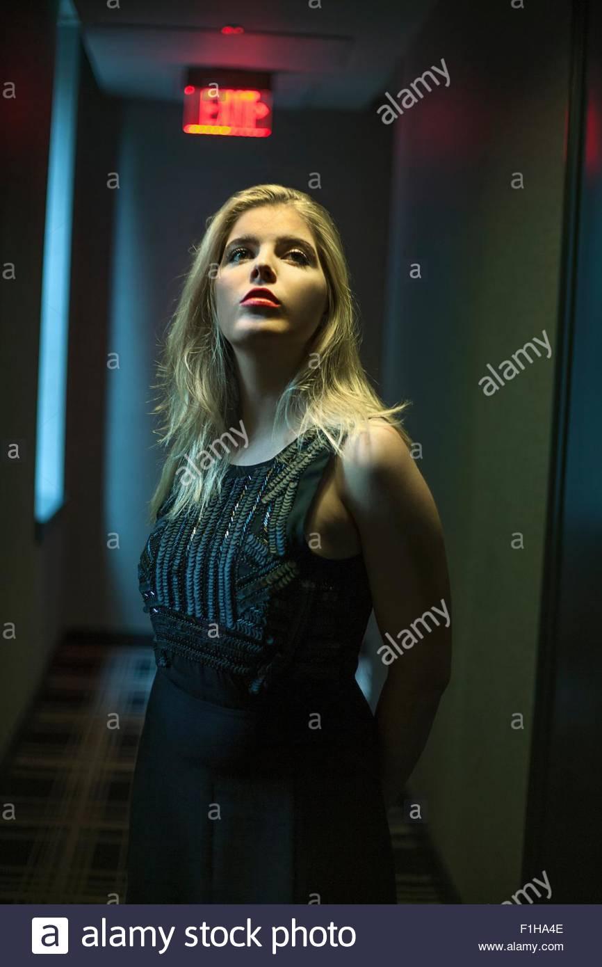 Retrato de hermosa rubia joven mirando hacia arriba en el pasillo oscuro Foto de stock