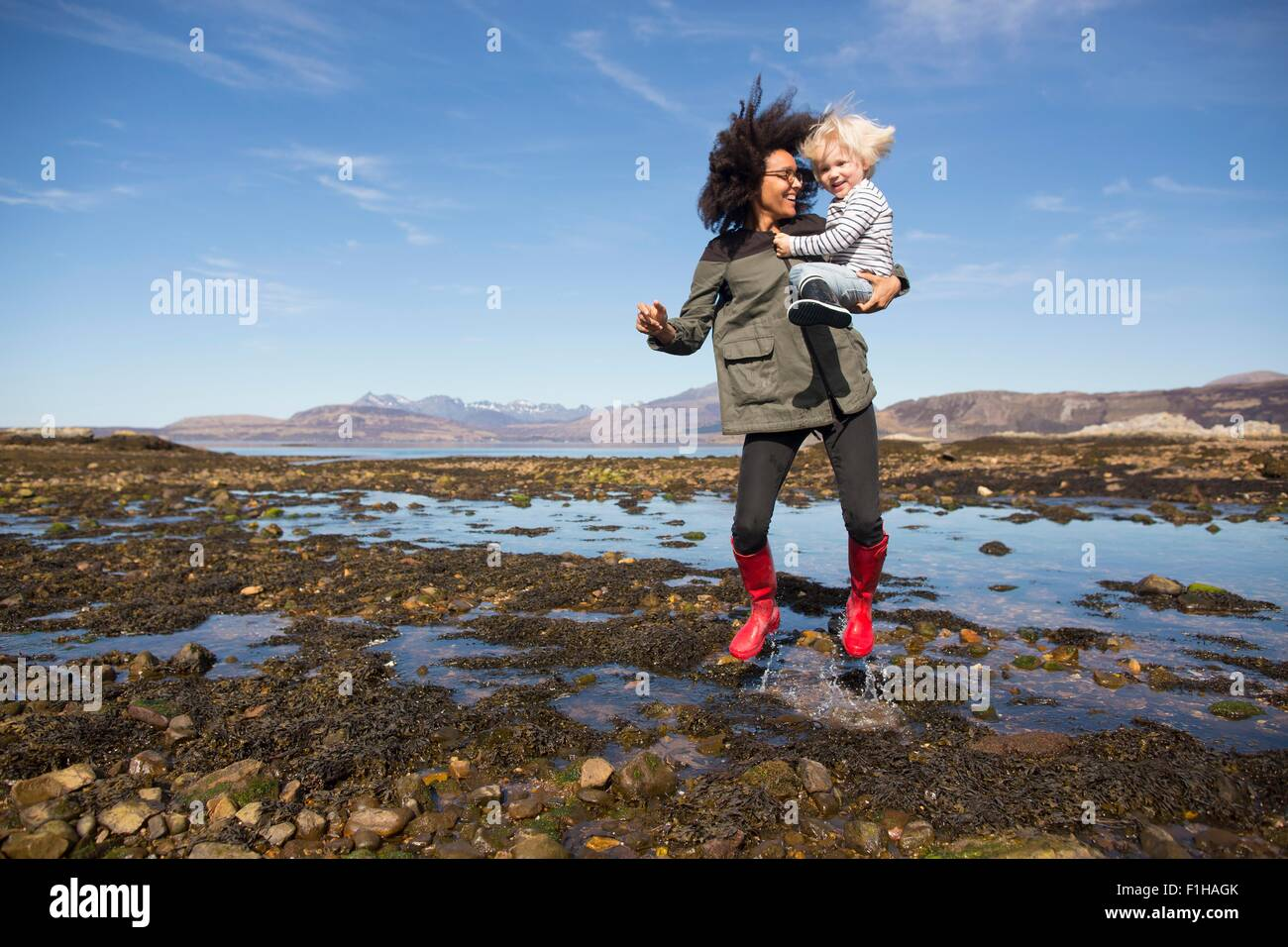 Madre sosteniendo hijo saltando en Loch Eishort, Isla de Skye, Hébridas, Escocia Imagen De Stock