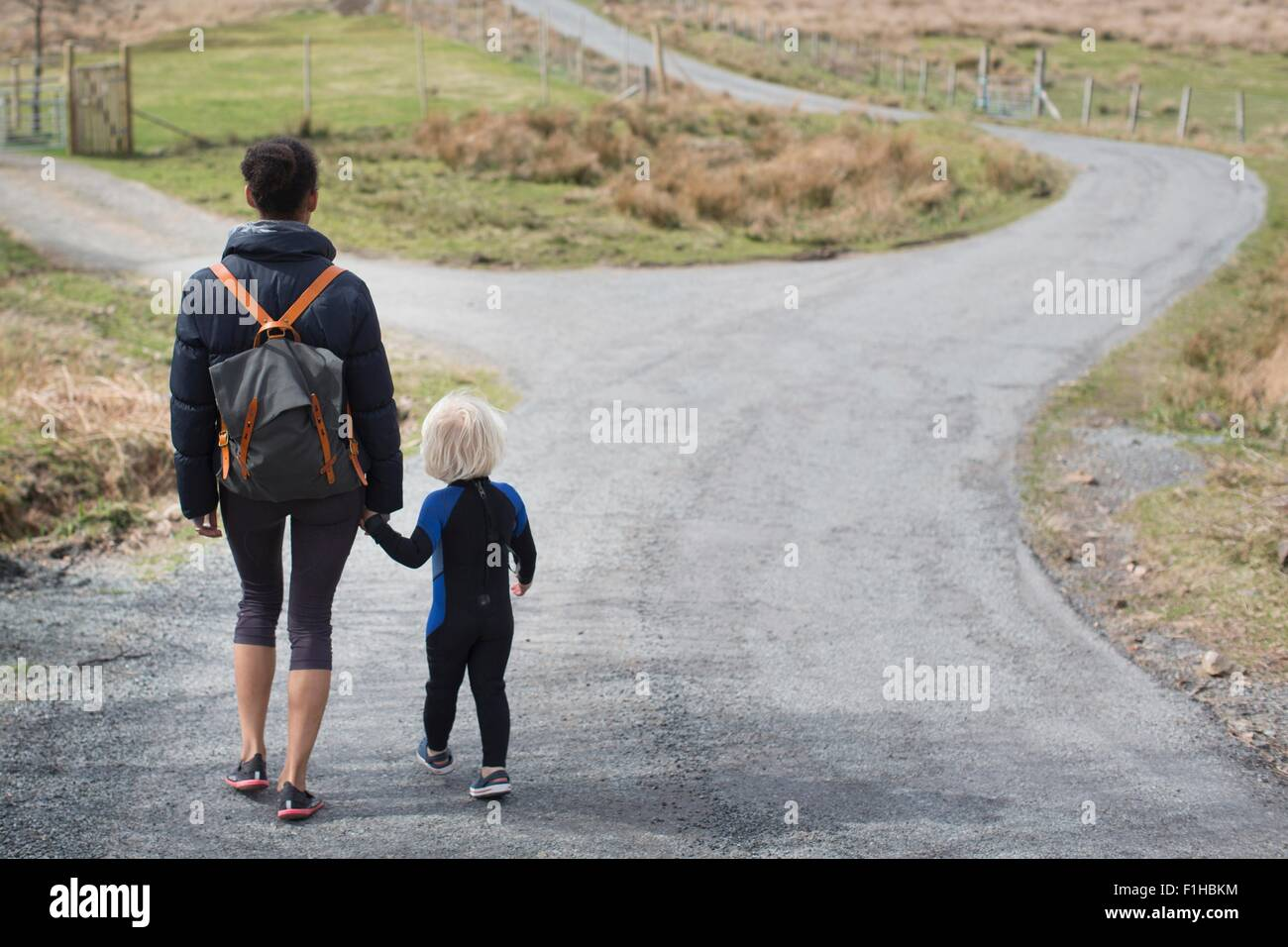 Madre e hijo caminando sobre country road tomados de las manos, vista trasera Foto de stock