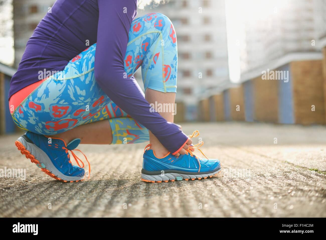 Vista recortada de mujer agacharse para atar las zapatillas de entrenamiento deportivo puntilla Imagen De Stock
