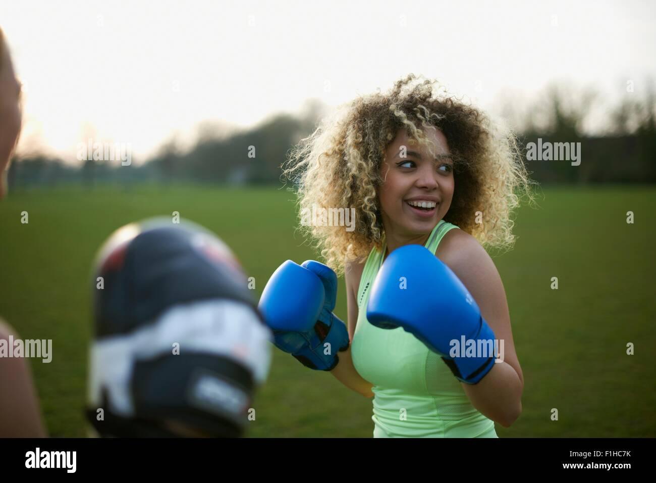 Dos mujeres que ejerzan con guantes de boxeo en el parque Imagen De Stock
