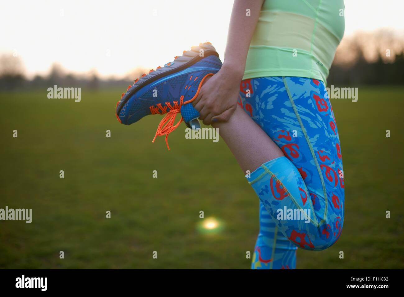 Imagen recortada de la mujer estirando la pierna para ejercer en estacionamiento Imagen De Stock