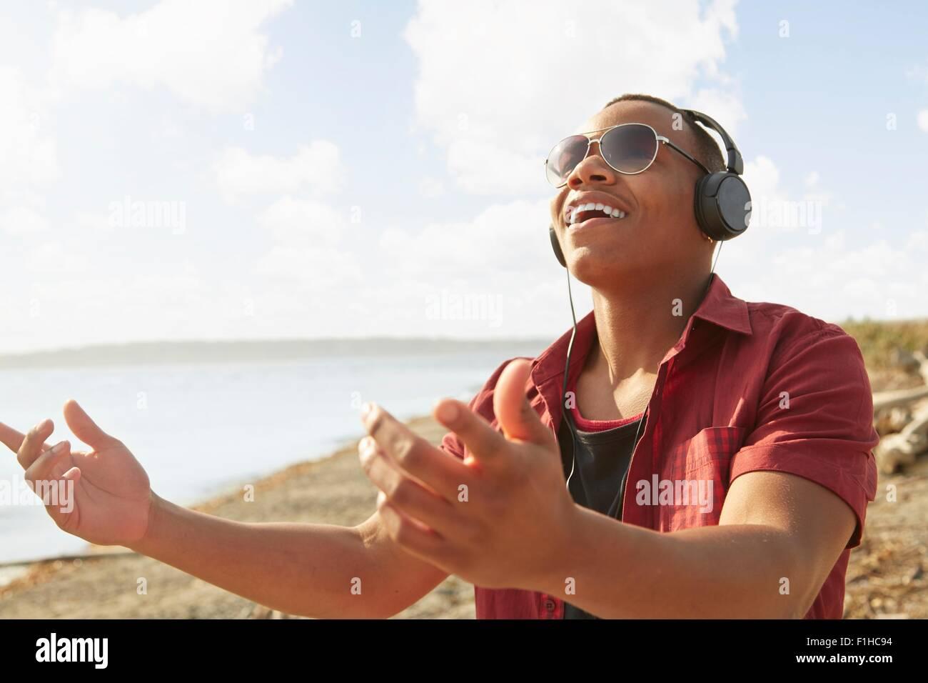 Joven en la playa usando audífonos y gafas de sol, los brazos levantados Imagen De Stock
