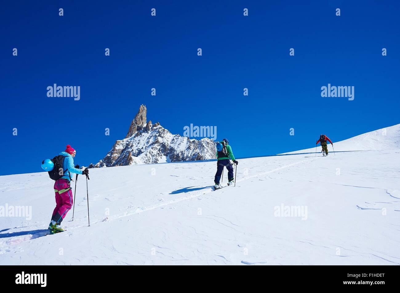 Tres adultos esquiadores subiendo Graian macizo del Mont Blanc, Alpes, Francia Imagen De Stock