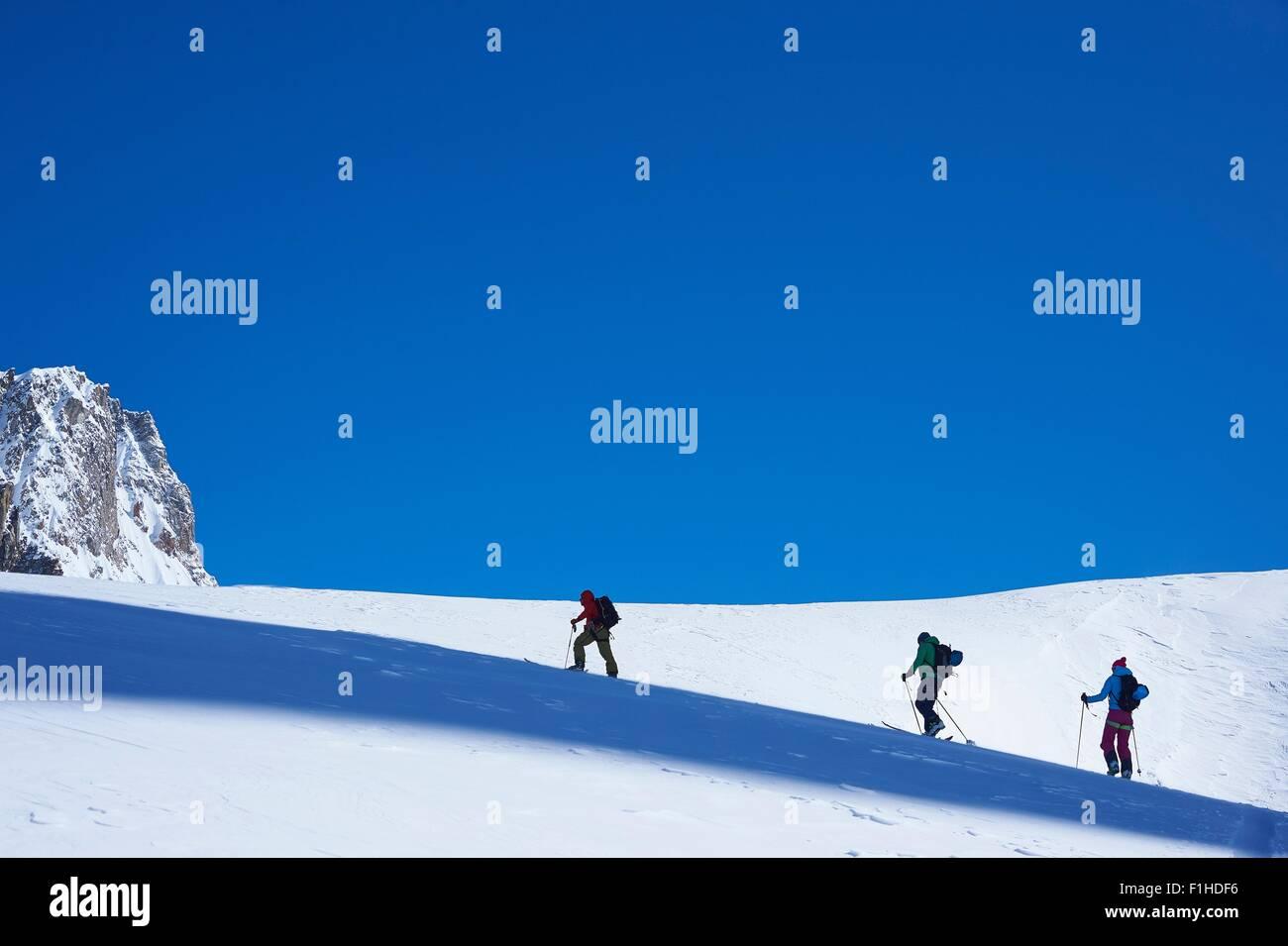 Ver siluetas de tres esquiadores subiendo Graian macizo del Mont Blanc, Alpes, Francia Imagen De Stock