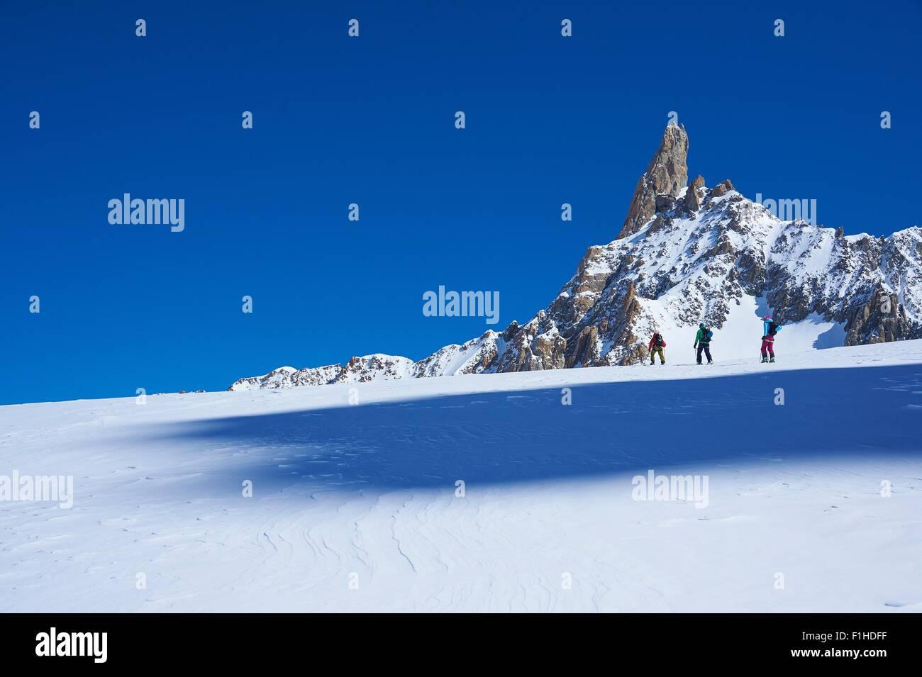 Vista lejana de tres esquiadores subiendo Graian macizo del Mont Blanc, Alpes, Francia Imagen De Stock