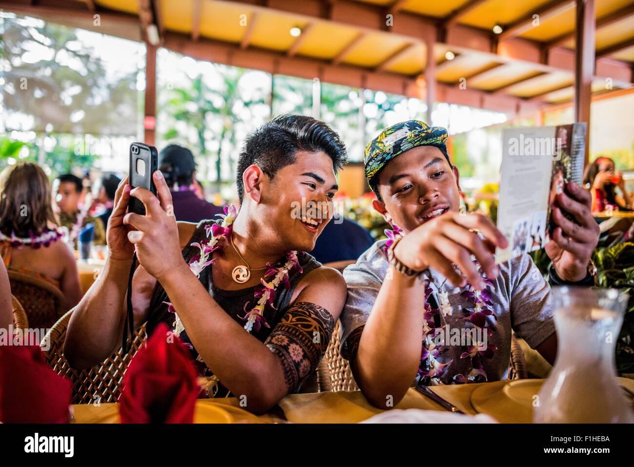 Dos hombres jóvenes lectura del menú en el Centro Cultural Polinesio, Hawaii, EE.UU. Foto de stock