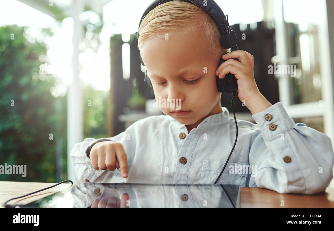 Chico escuchando su música seleccionada banda sonora que él ha elegido desactivar la pantalla táctil Imagen De Stock