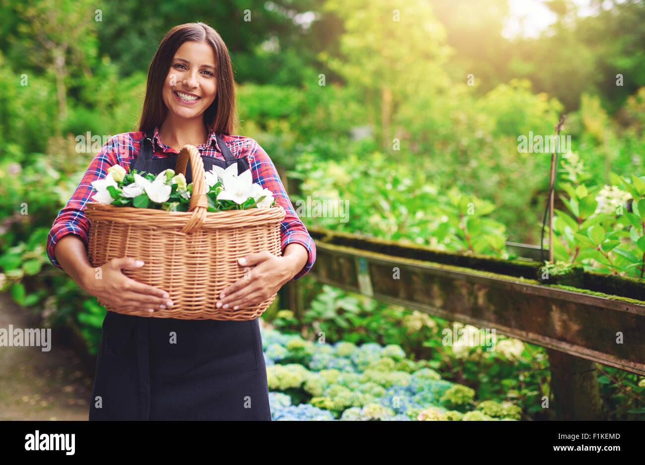 Mujer joven florista trabajar al aire libre en el vivero, recoger flores en un gran cesto de mimbre que sostiene Imagen De Stock