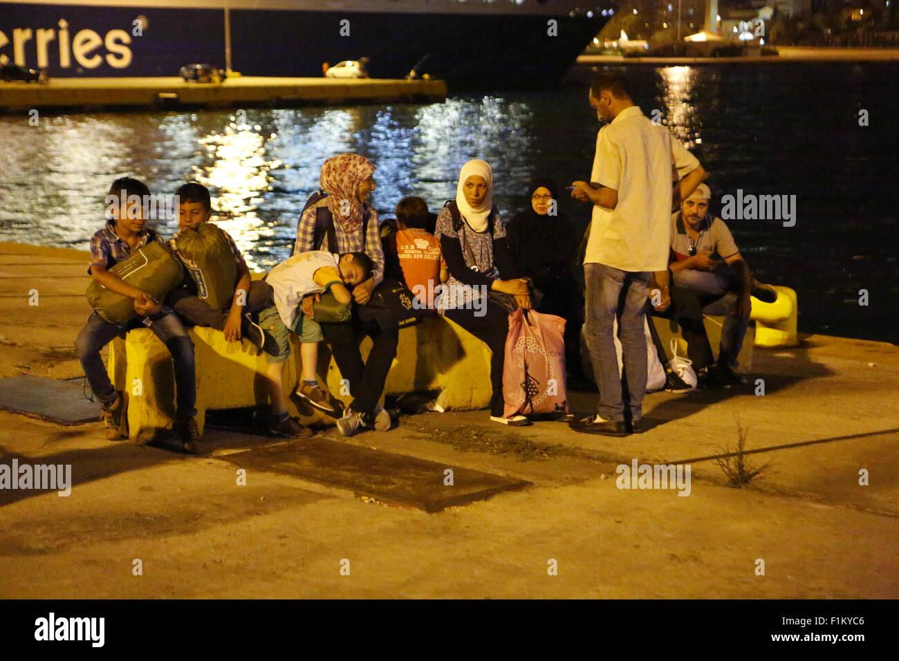 Atenas, Grecia. 3 de septiembre de 2015. Los refugiados sentarse en unas piedras sobre los muelles del puerto del Pireo, esperando el autobús para llevarlos a la estación de tren. Miles de refugiados llegaron en el puerto del Pireo a bordo el Gobierno fletó Tera jet ferry desde la isla griega de Lesbos. Cientos de refugiados, en su mayoría procedentes de Siria y Afganistán llegan a las islas griegas cada semana, añadiendo a la ya varios miles de refugiados ya en las islas griegas. Crédito: Michael Debets/Alamy Live News Foto de stock