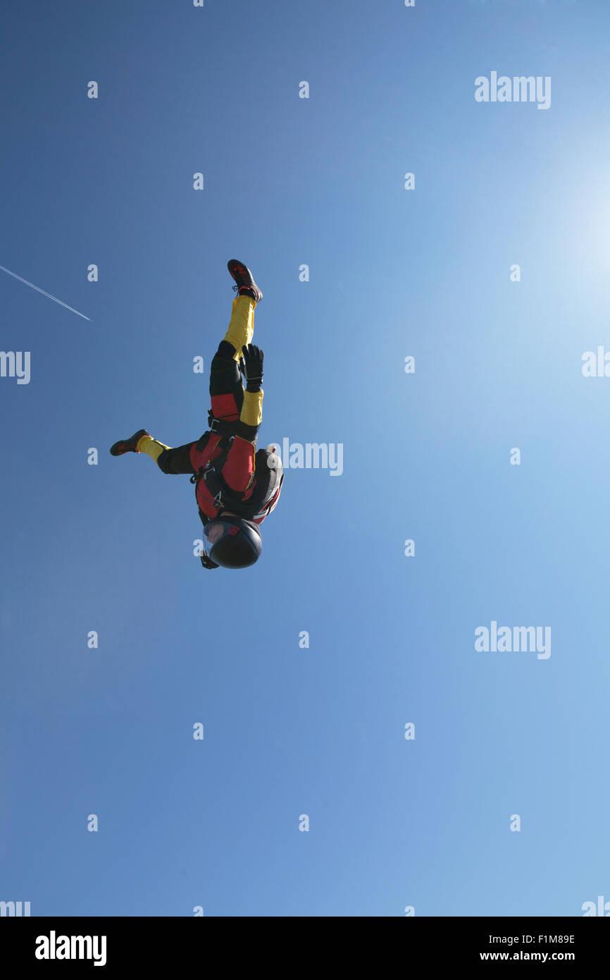 Este paracaidista chica está volando en una posición con la cabeza hacia abajo en el cielo azul, sin nubes. Imagen De Stock