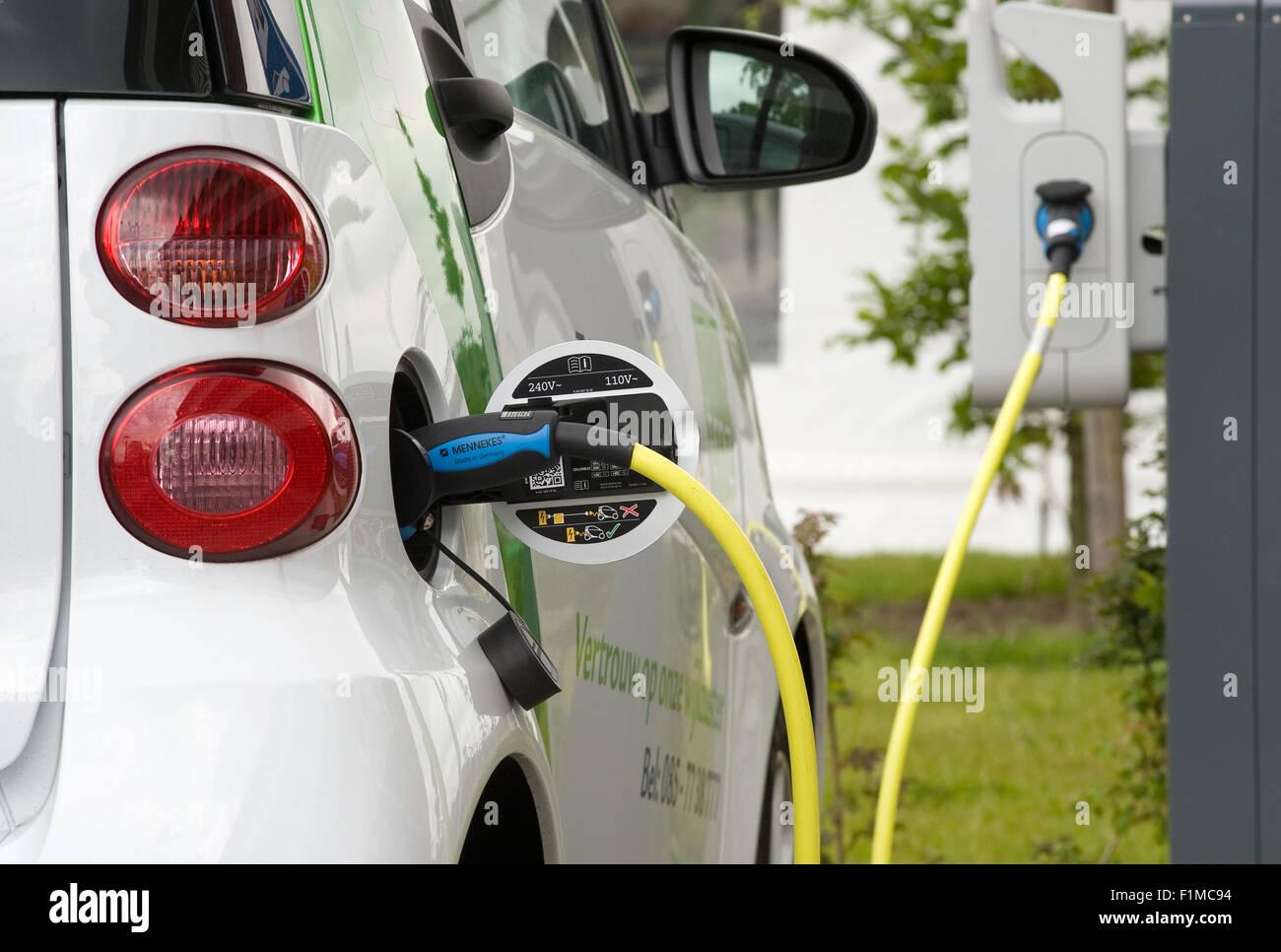 Un coche eléctrico está estacionado en un aparcamiento y se recarga en una estación de energía Imagen De Stock