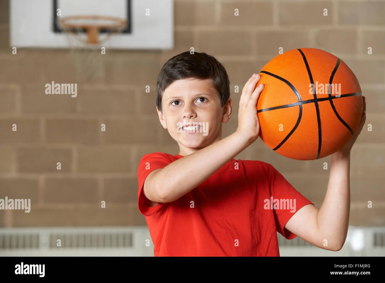 Boy Tiroteo durante la coincidencia de baloncesto en la escuela Gimnasio Imagen De Stock