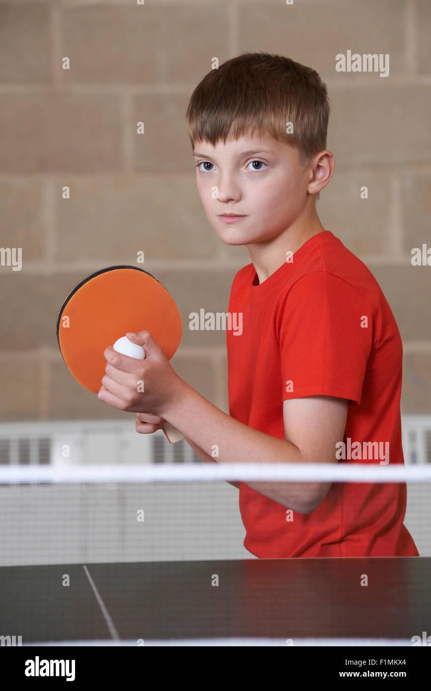 Chico jugando al tenis de mesa en la escuela Gimnasio Imagen De Stock