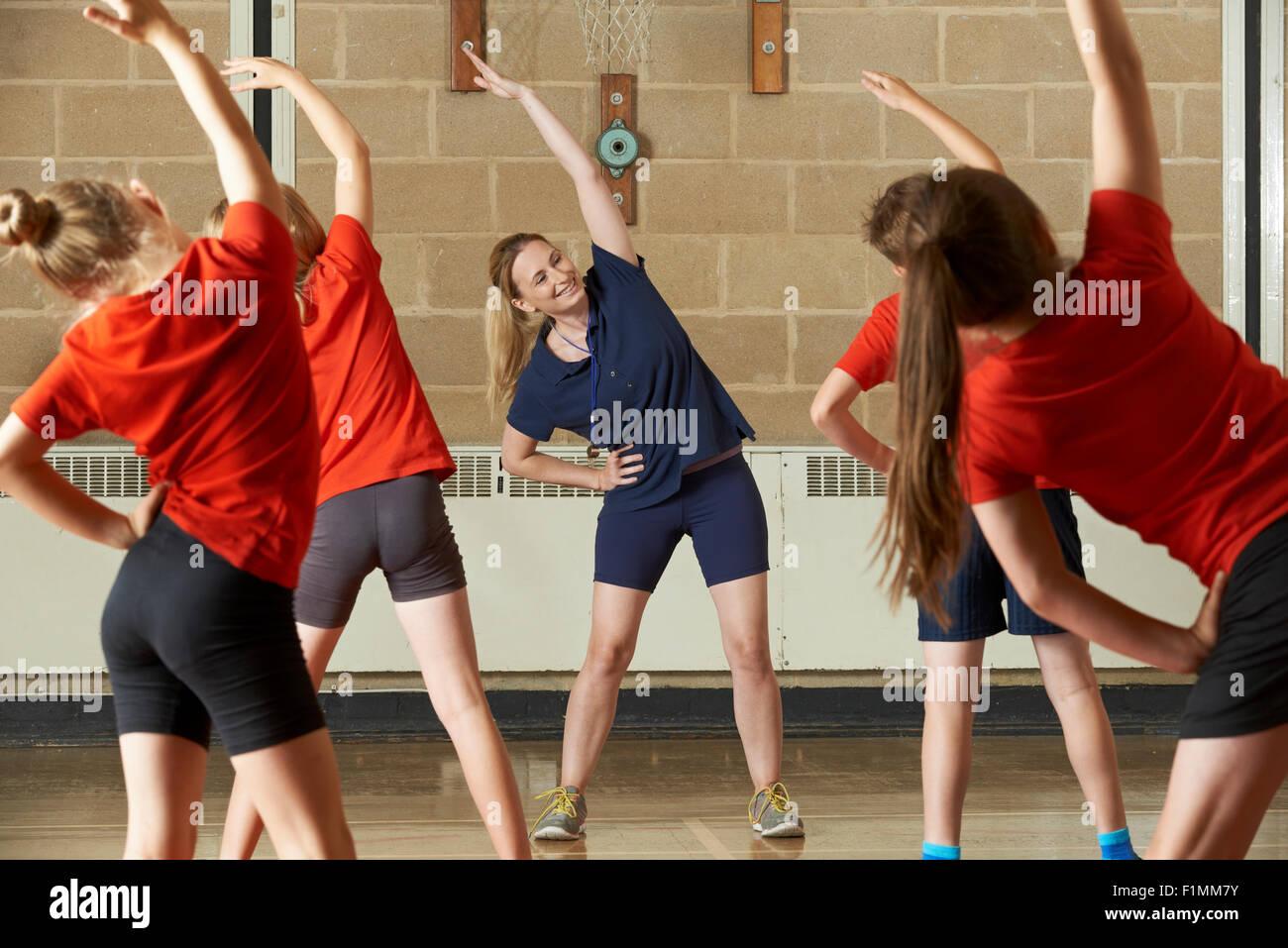 Profesor tomando clase de ejercicios en el gimnasio escolar Imagen De Stock