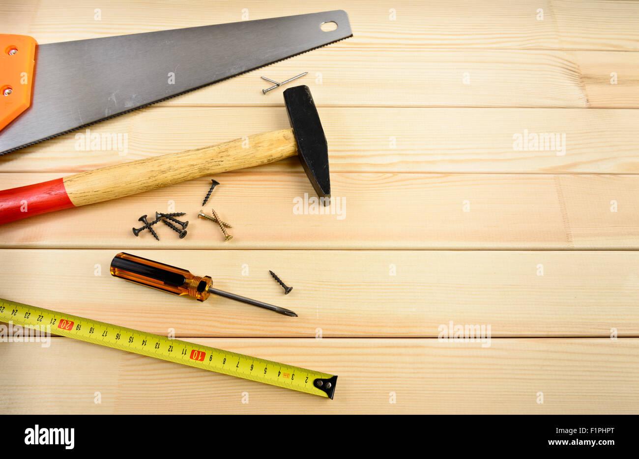 Vio, tornillo, cinta métrica y un martillo en la madera Imagen De Stock