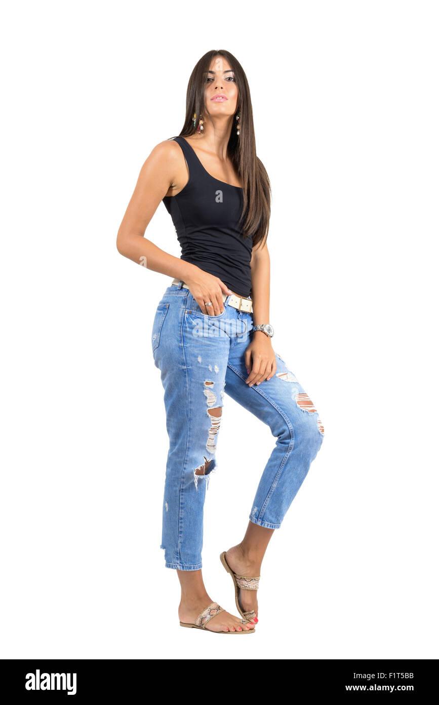 b6d4aa70d3 Joven Mujer casual en pantalones vaqueros rasgados posando en cámara.  Longitud de cuerpo completo retrato