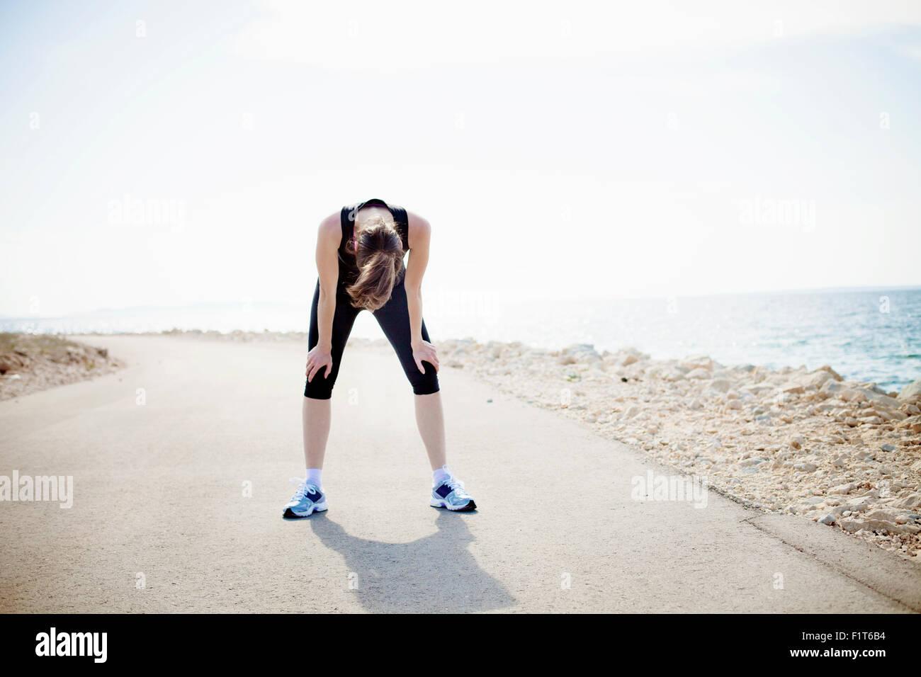 Mujer en ropa deportiva de pie en el waterfront ruta Imagen De Stock