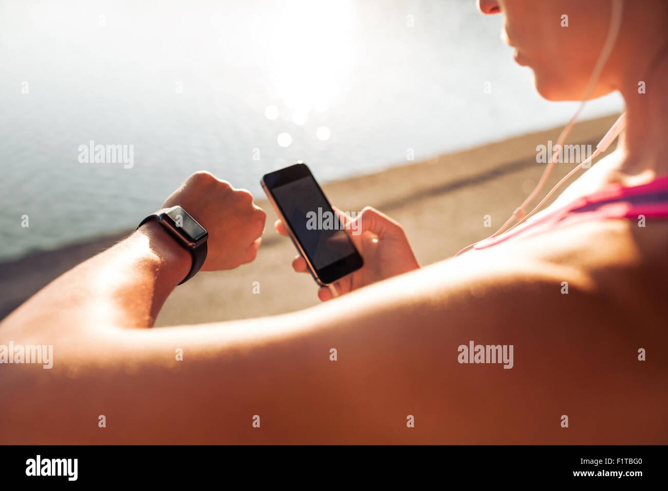 Mirando Sportswoman smartwatch y mantiene el teléfono inteligente en su otra mano, al aire libre. Hembra de Imagen De Stock