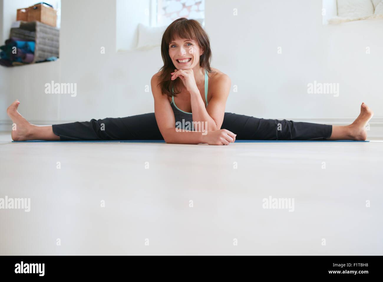 Mujer feliz haciendo amplio ángulo de inclinación hacia adelante sentado yoga en el gimnasio. Fitness Imagen De Stock