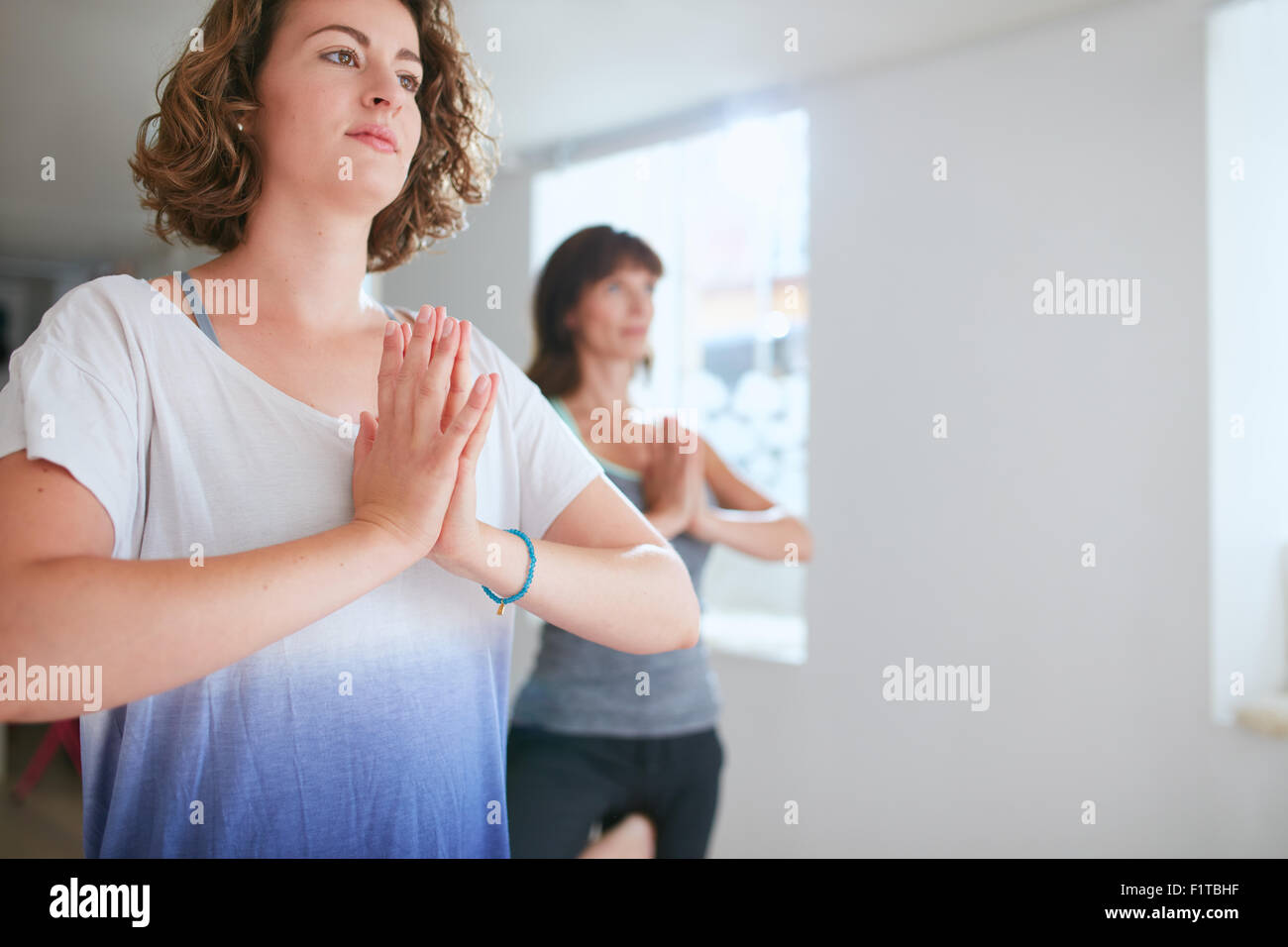 Retrato de mujer joven con su entrenador de fitness en segundo plano haciendo ejercicio de yoga. Realizar la postura Imagen De Stock