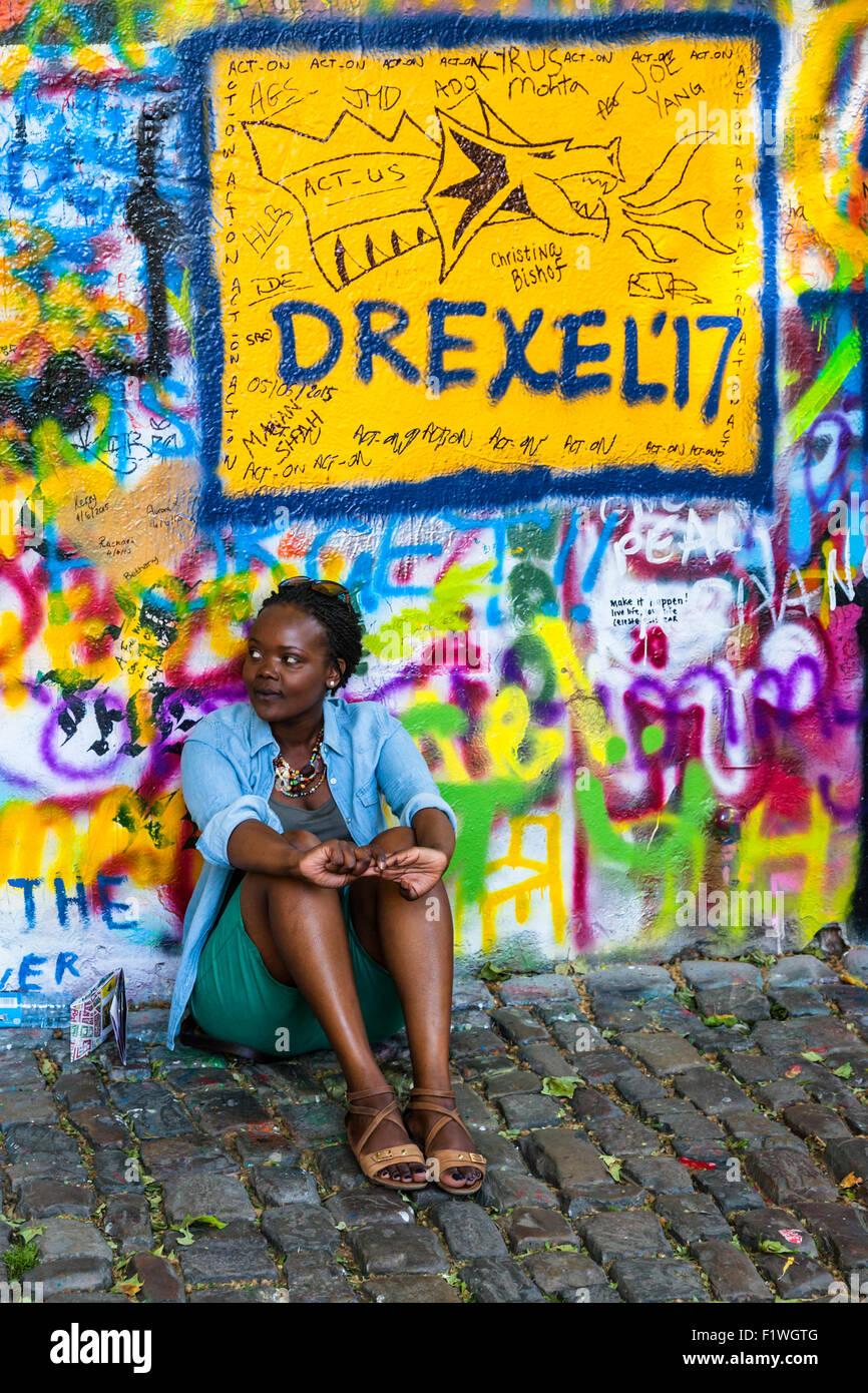 Joven turista sentado al lado de la muro John Lennon, Praga, República Checa. Foto de stock