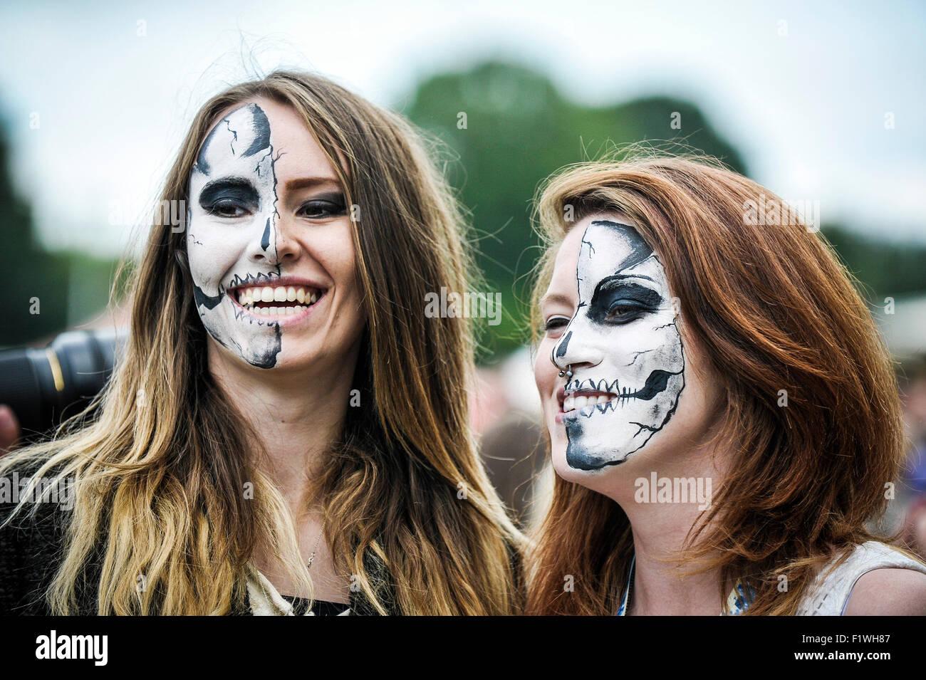 Dos espectadores con sus caras pintadas en junto al pueblo en el Festival de Brighton. Foto de stock