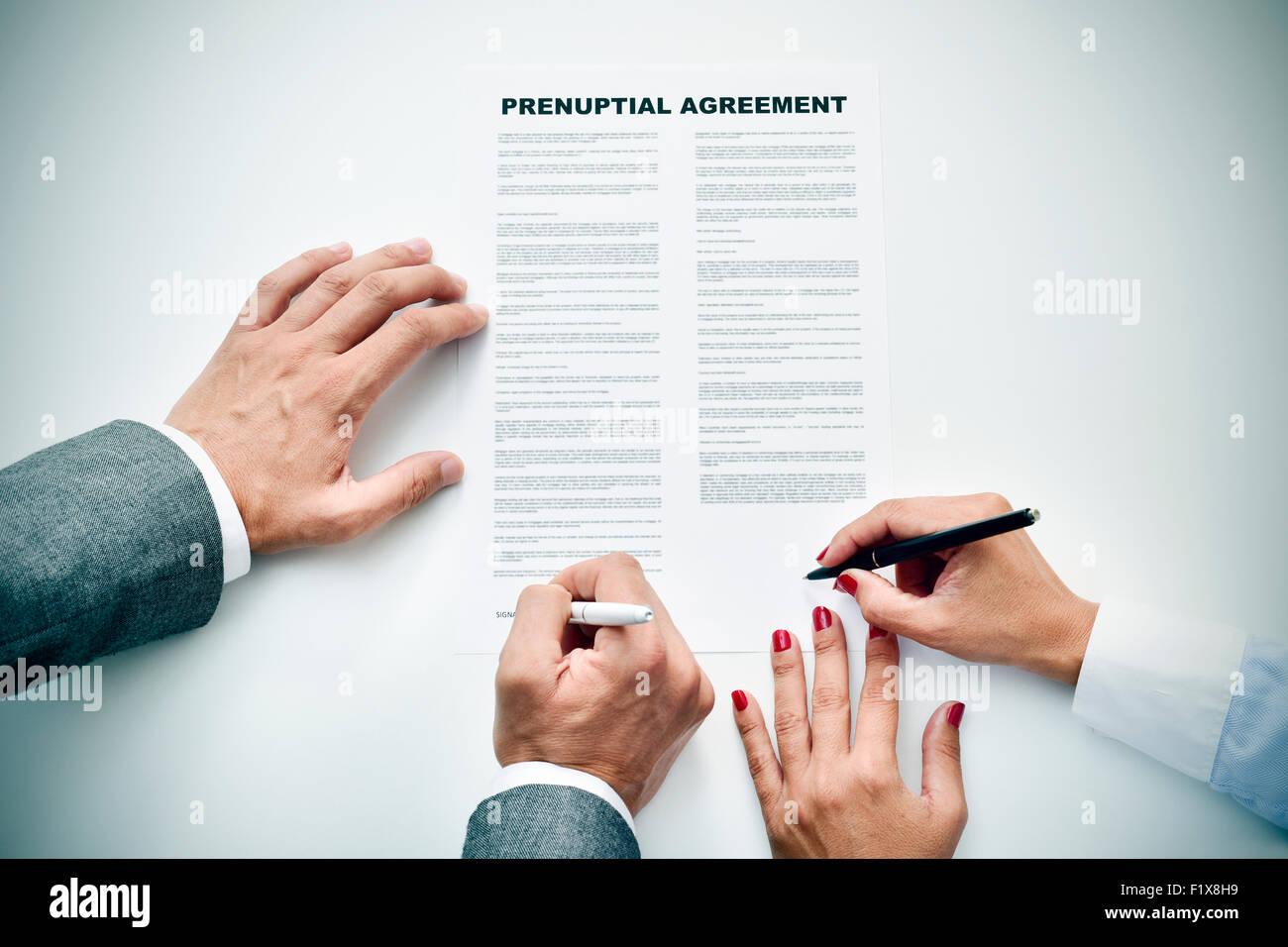 Primer plano de un joven y una joven firma un acuerdo prematrimonial Imagen De Stock
