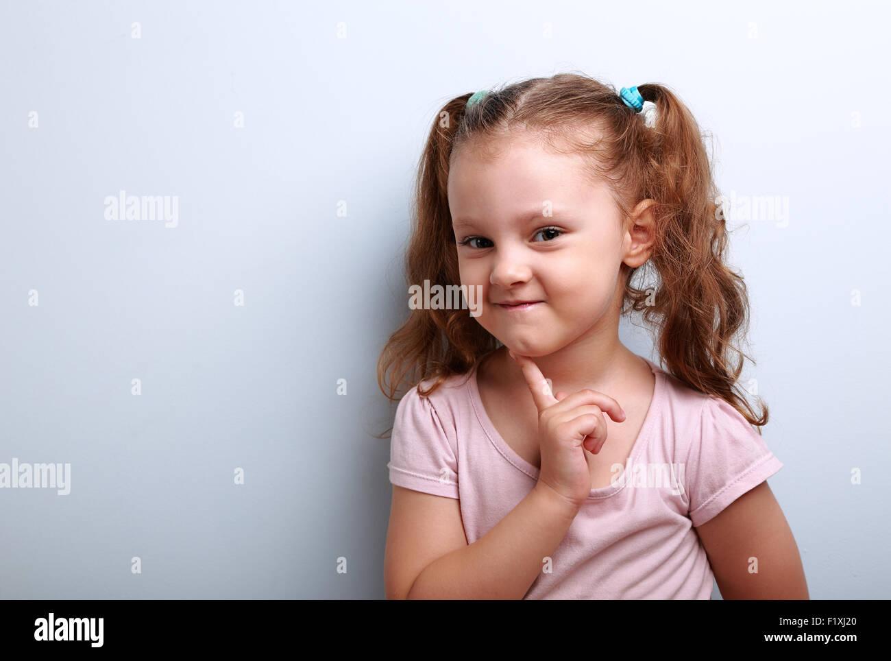 Astucia pensando en pequeño chico chica con dedo cerca de cara sobre fondo azul, con copia espacio vacío Imagen De Stock