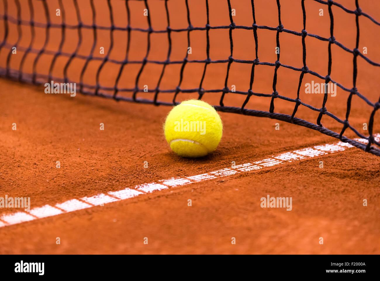 Amarillo pelota de tenis en una cancha de arcilla roja Imagen De Stock