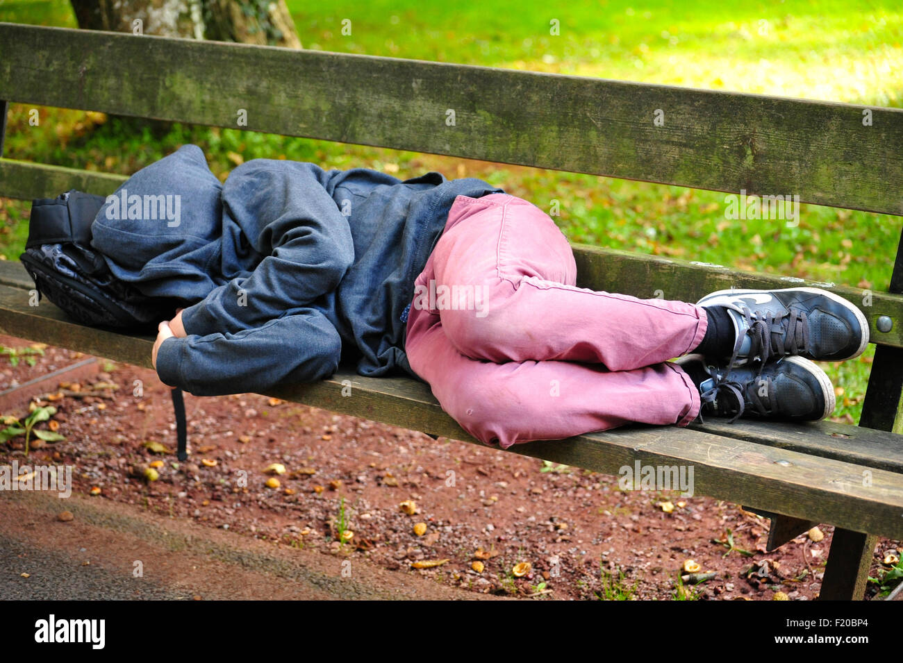 Niño dormido sobre un banco del parque Fotografía de stock - Alamy