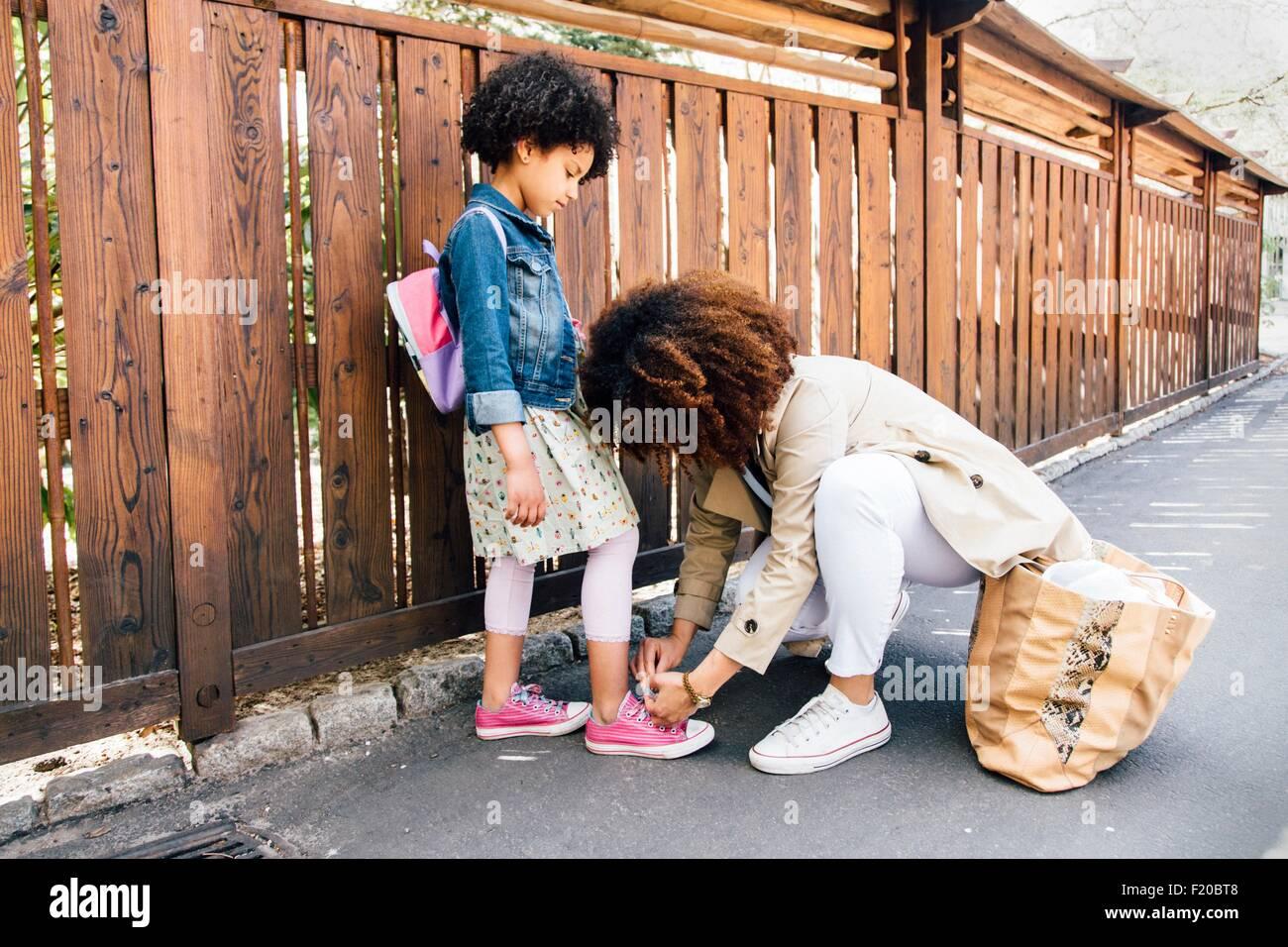 La madre de rodillas por valla hijas shoelace atado Imagen De Stock