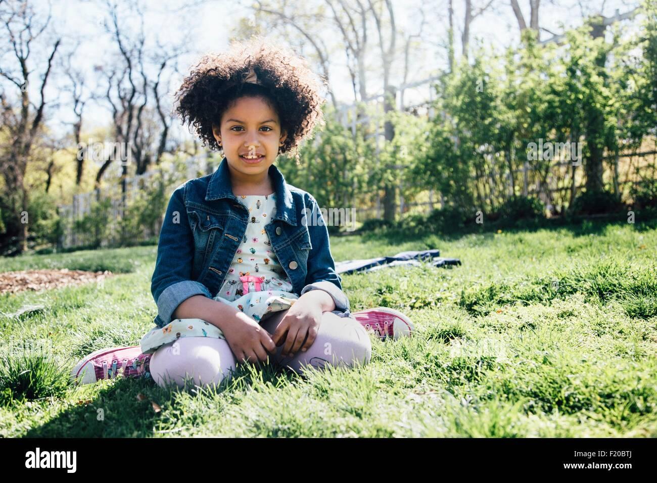 Vista frontal de la chica sentada en el pasto, mirando a la cámara Imagen De Stock
