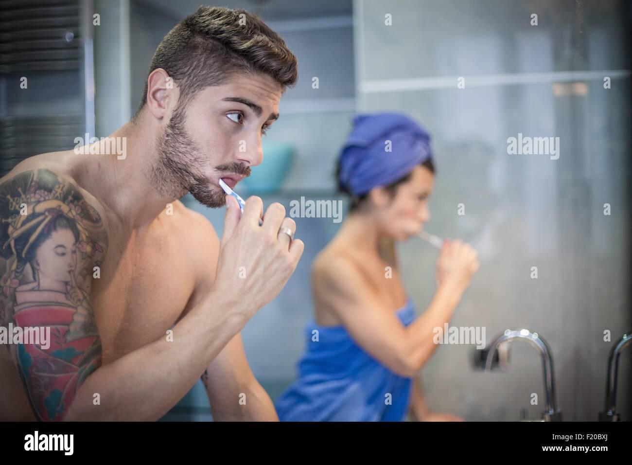 Pareja joven cepillarse los dientes en el baño. Imagen De Stock