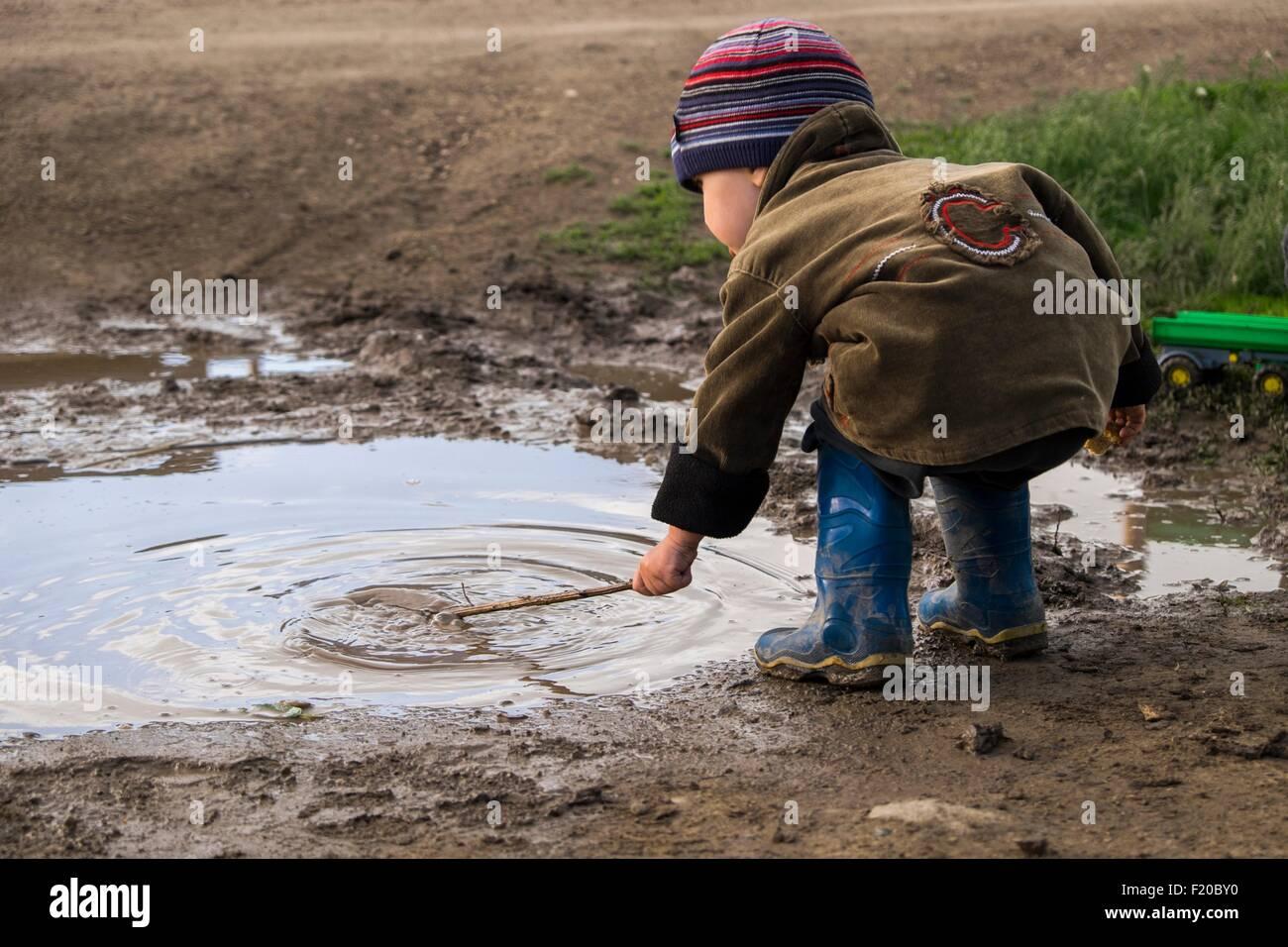 Usando botas de goma niño masculino jugando con bastón en charco Foto de stock