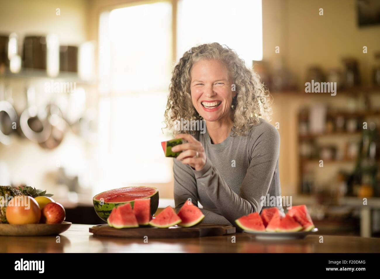 Retrato de mujer madura comiendo sandía en la cocina Imagen De Stock