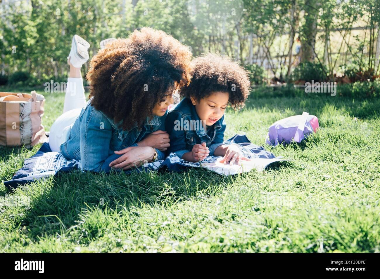 Madre e hija acostada en frentes, uno al lado del otro, libro de lectura juntos Imagen De Stock