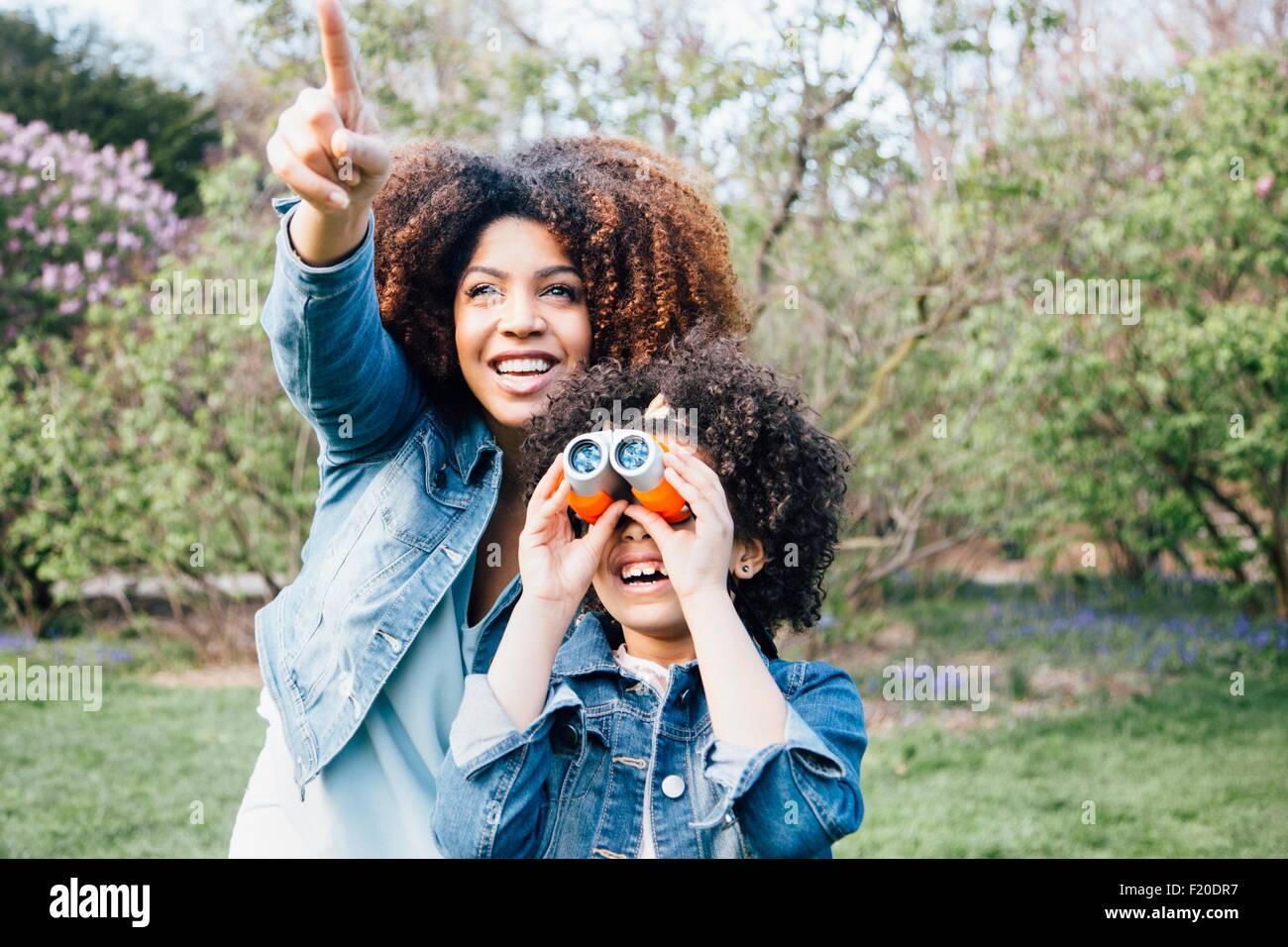 Madre e hija utilizando binoculares, mirando hacia arriba, apuntando Foto de stock