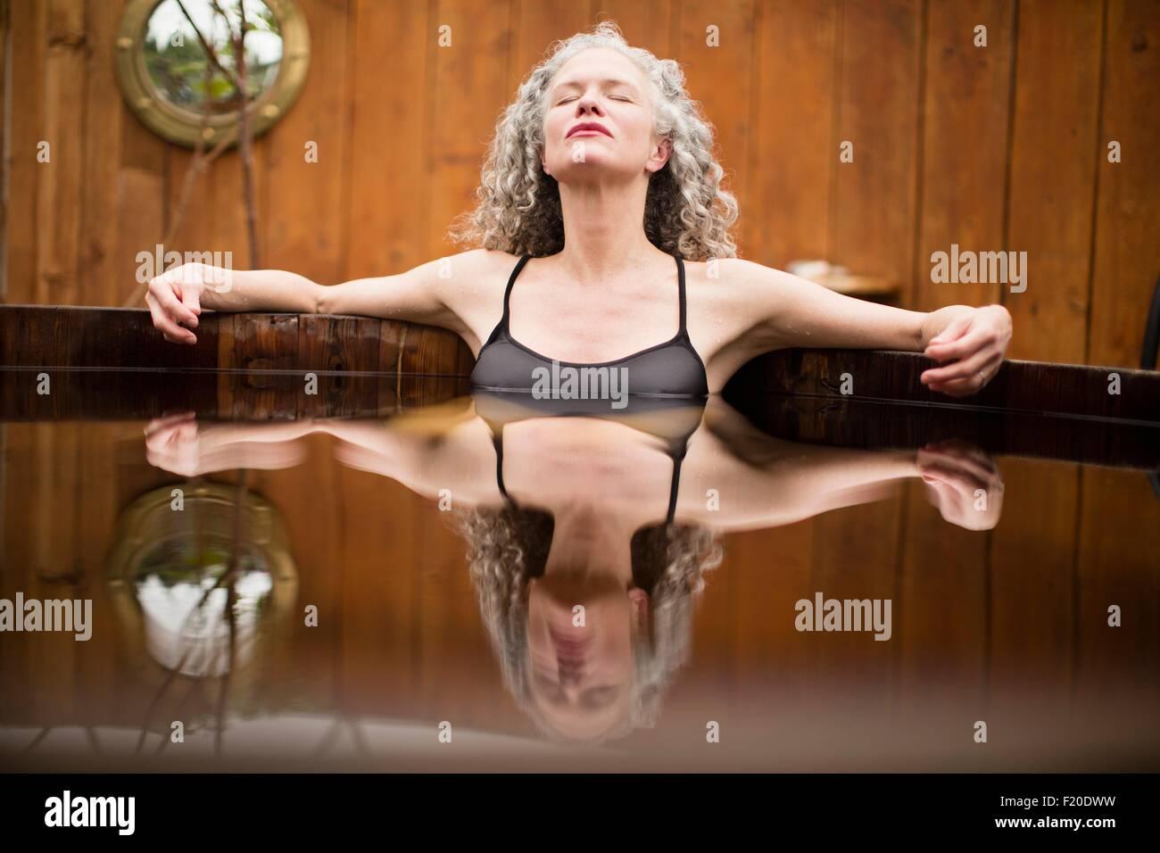Mujer madura, meditando con los ojos cerrados en un ofuro en eco retreat Foto de stock