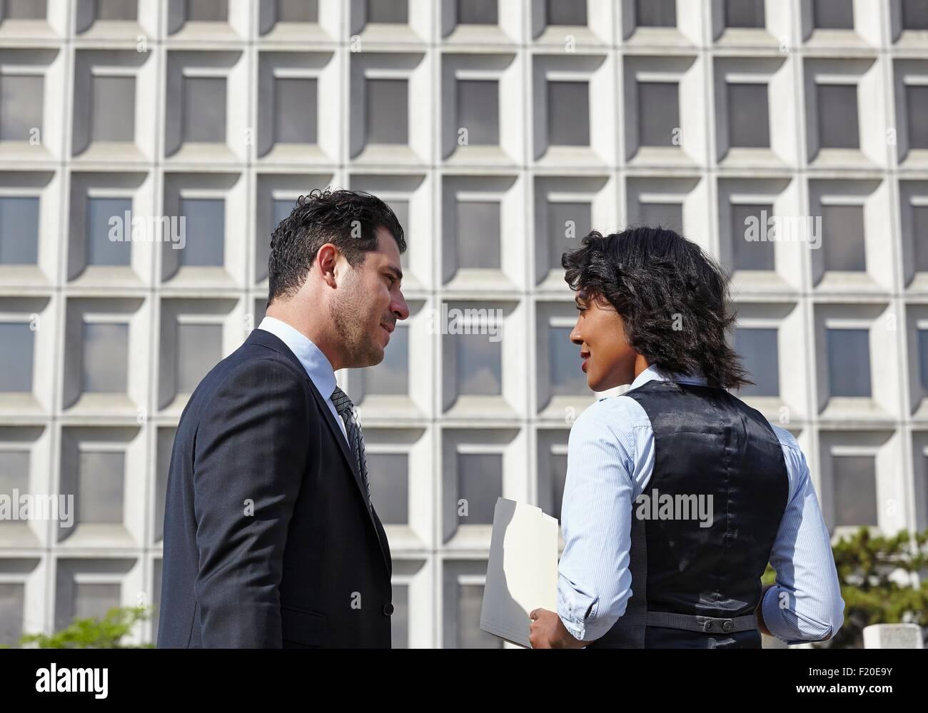 La gente de negocios de pie hablar cara a cara, sosteniendo el papeleo, de cintura para arriba Imagen De Stock