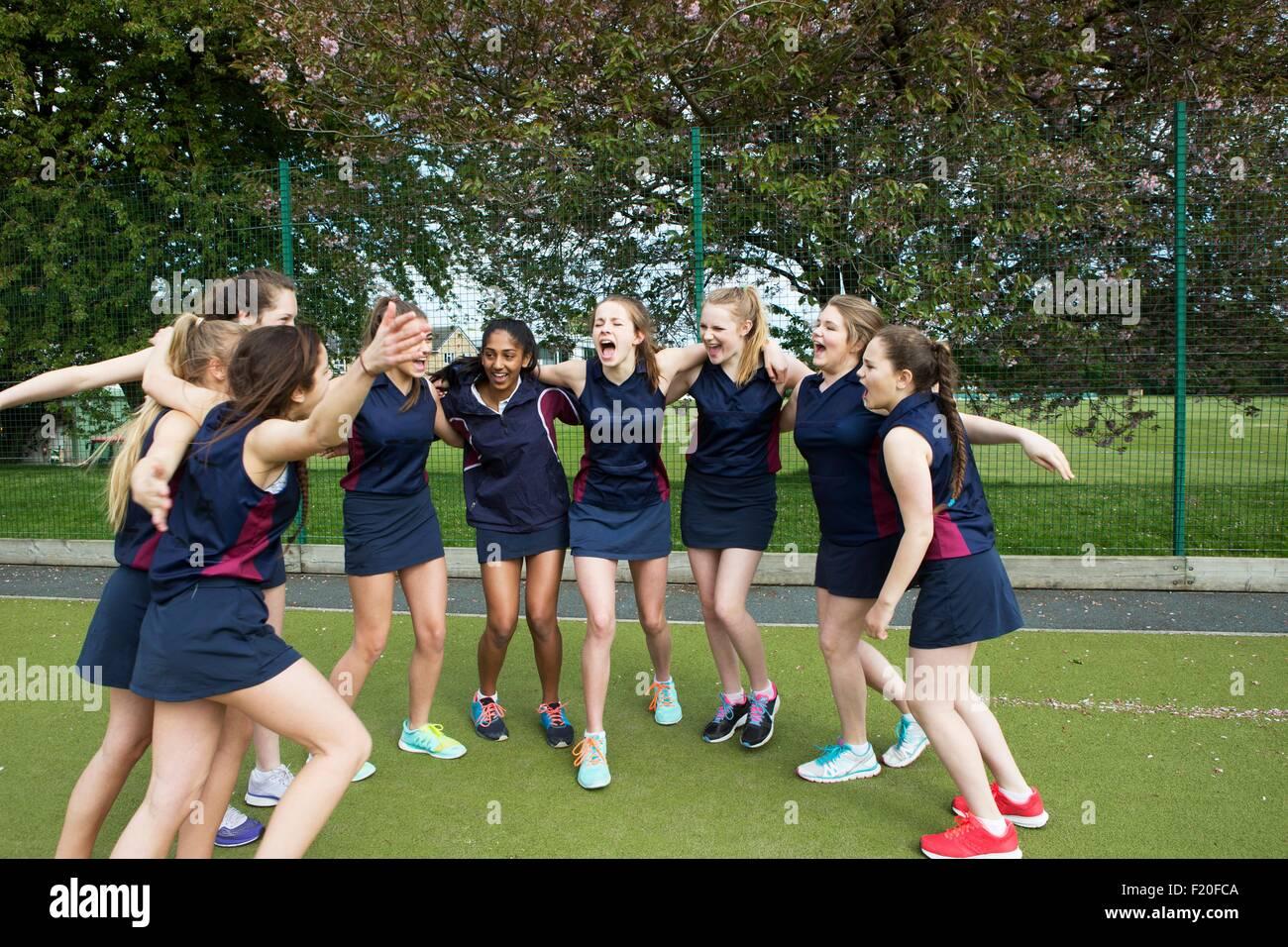 Grupo de estudiantes mujeres en el campo de deportes, brazos alrededor Imagen De Stock