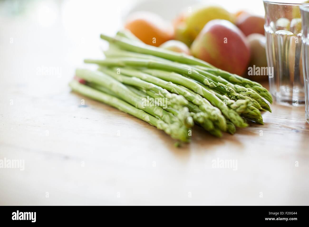 Espárragos, frutas, vaso para beber en la mesa de comedor Foto de stock